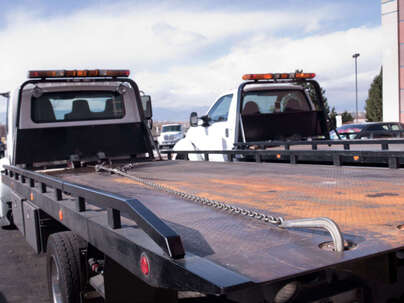 Two tow trucks side by side with empty trays