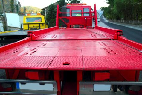 view from the back of a red tow truck with an empty tray