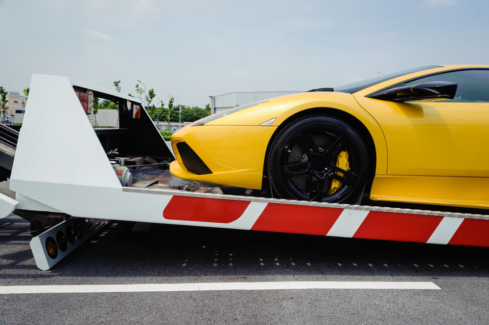 side view of a yellow sports car getting loaded onto a tilt tray tow truck