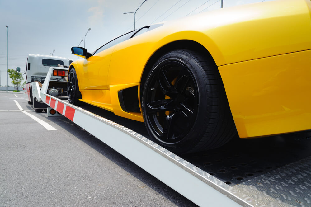 a rear angle of a yellow sports car being loaded onto a flat bed tow truck